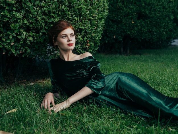Een vrouw in een groene jurk ligt op het gazon van de luxe charme van de buitenlucht. hoge kwaliteit foto