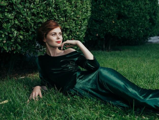 Een vrouw in een groene jurk ligt op het gazon van de luxe charme van de buitenlucht.