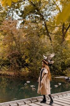Een vrouw in een herfstjas in een stadspark in de herfst tijdens een wandeling