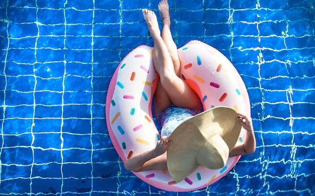 Een vrouw in een hoed ontspant op een opblaasbare cirkel in het zwembad.