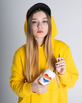 Een vrouw in een hoodie en een zwarte pet houdt een kartonnen beker in haar handen met de woorden liefde is liefde en een hart met een regenboog lgbt