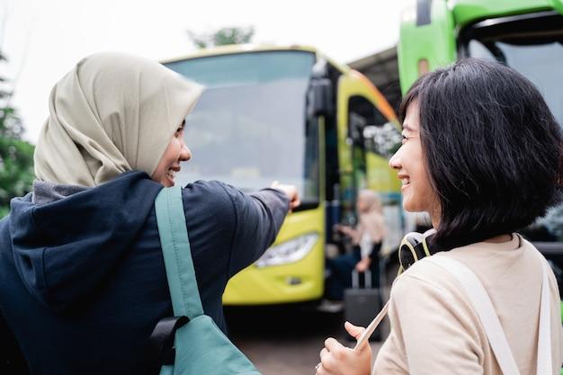 Een vrouw in een hoofddoek met een vinger die naar de bus wijst terwijl ze met een vrouw met koptelefoon praat terwijl ze met de bus gaat
