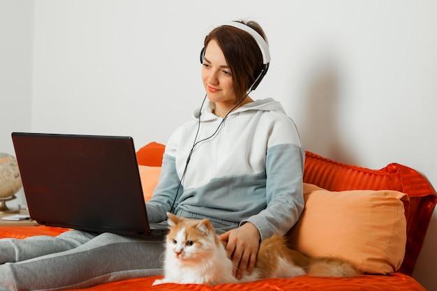 Een vrouw in een huiselijk licht pak met een koptelefoon op een laptop op een bank zittend op het bed met een kat