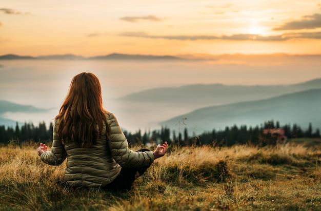 Een vrouw in een jas zit op het gele gras bovenop een berg en mediteert.