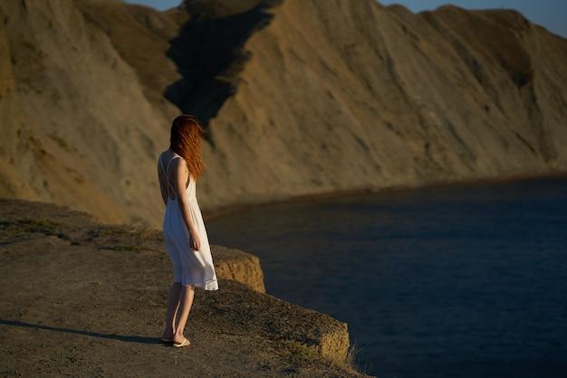 Een vrouw in een jurk loopt in de zomer langs het strand in de natuur in de bergen