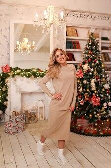 Een vrouw in een jurk poseren bij een boom en een open haard in een licht interieur thuis in de avond