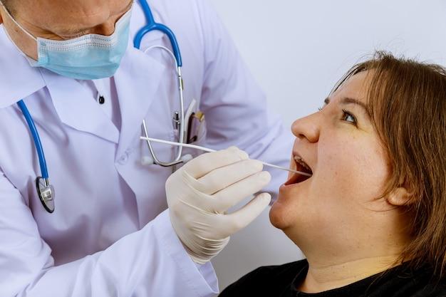 Een vrouw in een klinische setting die door een gezondheidswerker wordt schoongemaakt om vast te stellen of hij het coronavirus covid-19 heeft opgelopen.