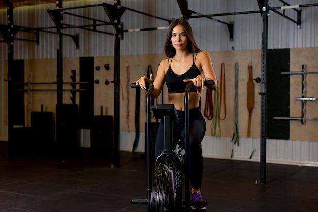 Een vrouw in een korte zwarte top en een zwarte sportbroek zit op een machine die een voetoefening uitvoert in de sportschool.