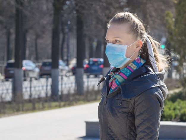 Een vrouw in een medisch masker op straat in de stad