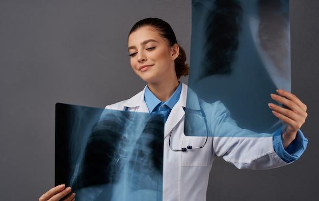 Een vrouw in een medische jurk onderzoekt röntgenstralen op een grijze achtergrond. hoge kwaliteit foto