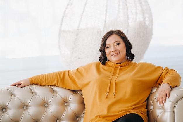 Een vrouw in een oranje hoodie zit op een witte bank