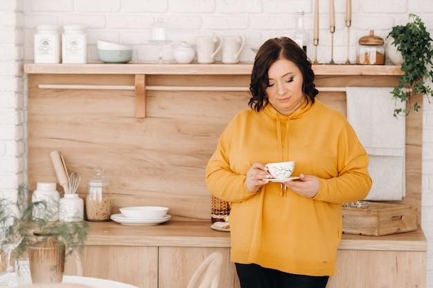 Een vrouw in een oranje sweater drinkt thuis koffie in de keuken.