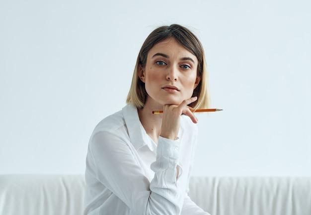 Een vrouw in een overhemd met documenten in haar handen zit binnenshuis op een bank