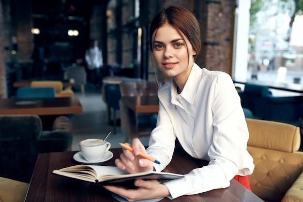 Een vrouw in een overhemd met een notitieboekje en een pen in haar hand zit aan een tafel