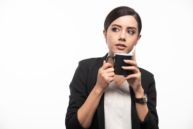 Een vrouw in een pak met een kopje koffie in de hand op een witte muur.