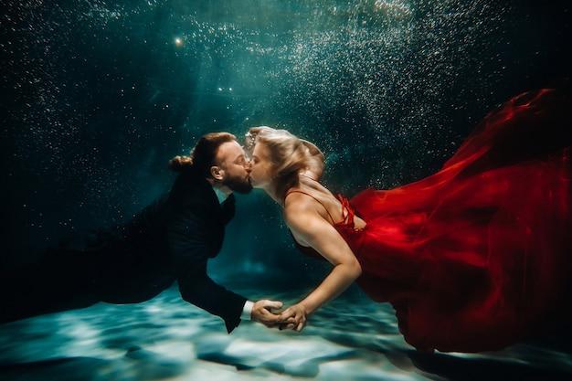 Een vrouw in een rode jurk en een man in een pak kussen onder water. een paar drijft onder water.