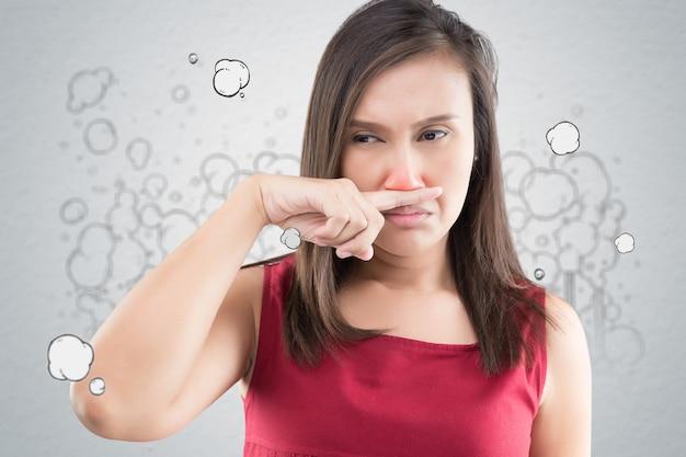Een vrouw in een rode jurk komt in haar neus terecht door een slechte geur