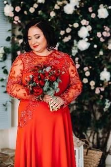 Een vrouw in een rode jurk staat en houdt een boeket rode rozen en aardbeien in het interieur.