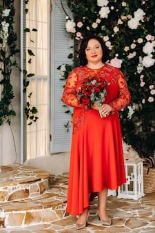 Een vrouw in een rode jurk staat en houdt een boeket rode rozen en aardbeien in het interieur Premium Foto
