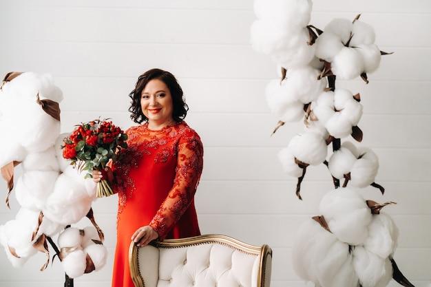 Een vrouw in een rode jurk staat en houdt een boeket rode rozen en aardbeien in het interieur