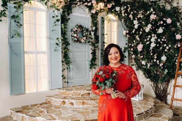 Een vrouw in een rode jurk staat en houdt een boeket rode rozen en aardbeien vast