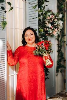 Een vrouw in een rode jurk staat en houdt een boeket rode rozen en bessen in het interieur