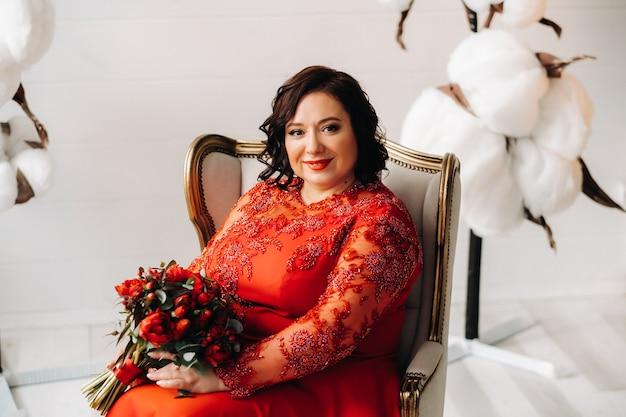 Een vrouw in een rode jurk zit in een stoel en heeft een boeket rode rozen en aardbeien in het interieur.