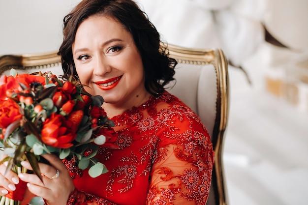 Een vrouw in een rode jurk zit in een stoel en houdt een boeket rode rozen en aardbeien in het interieur.