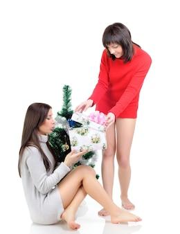 Een vrouw in een rode jurk zit op de vloer bij een kerstboom. meisje in een grijze jurk poseren met een cadeau in haar handen