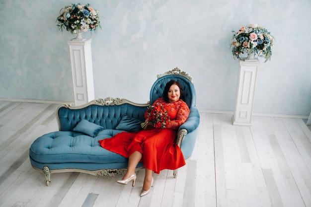 Een vrouw in een rode jurk zit op een bank en heeft een boeket rode rozen en aardbeien in het interieur.