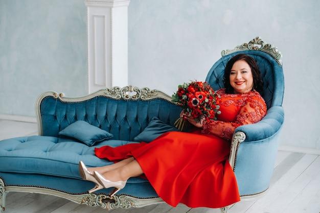 Een vrouw in een rode jurk zit op een bank en houdt een boeket rode rozen en aardbeien in het interieur.