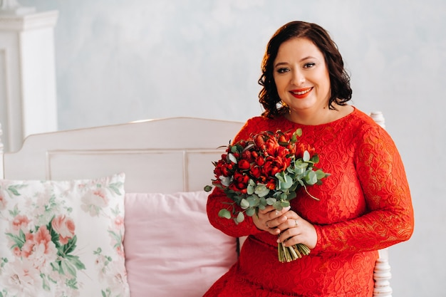 Een vrouw in een rode jurk zit op een bank en houdt een boeket rode rozen en bessen in het interieur.