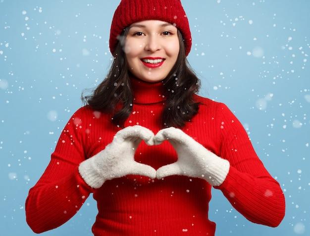 Een vrouw in een rode trui, wanten en een hoed vouwde haar handen in een hartplooi en glimlachte. tegen het oppervlak van vallende sneeuw
