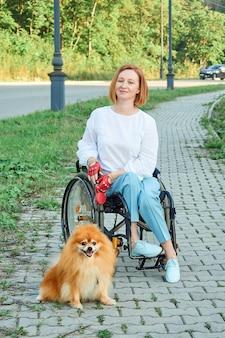 Een vrouw in een rolstoel loopt met haar hond buiten. internationale dag van mensen met een handicap