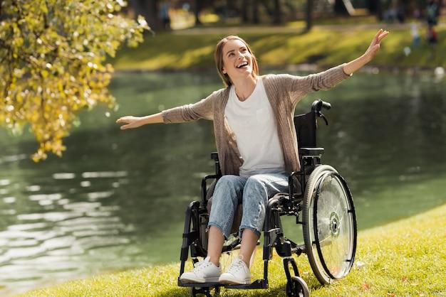 Een vrouw in een rolstoel zit aan de oever van een meer.