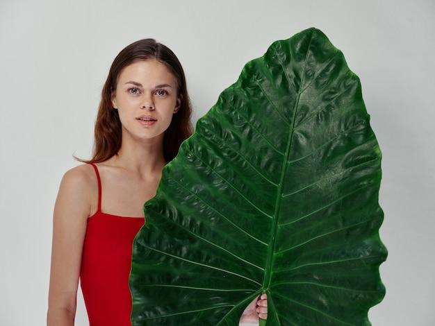 Een vrouw in een rood t-shirt heeft een groen blad in haar hand, een schone huid en een natuurlijke uitstraling