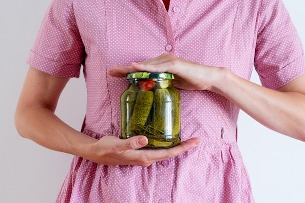Een vrouw in een roze jurk houdt een pot augurken vast. bewaartijd, herfstoogst, verse boerderijproducten