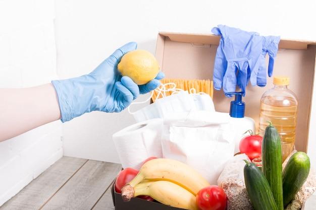 Een vrouw in een rubberen handschoen takt een citroen in een doos met voedsel en hygiëneproducten voor een donatie