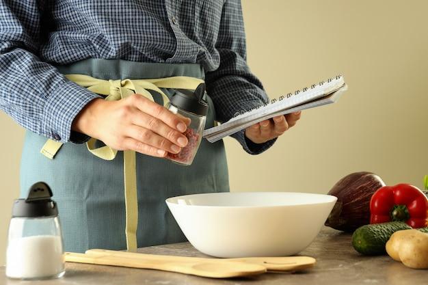 Een vrouw in een schort houdt een receptenboek vast en een kruiden- en kooktoestel