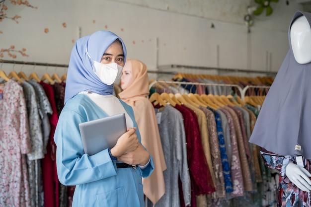Een vrouw in een sluier die een blauw masker draagt en een kussen vasthoudt, staat naast een mannequin