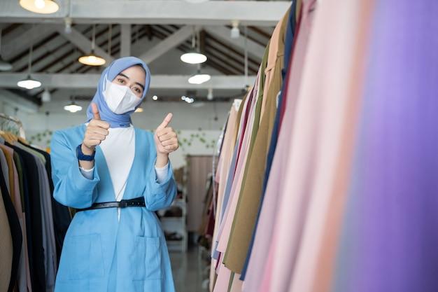 Een vrouw in een sluier die een blauw masker draagt met duimen omhoog terwijl ze staat