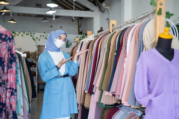 Een vrouw in een sluier die een blauw masker draagt met huidige handen iets gebaar