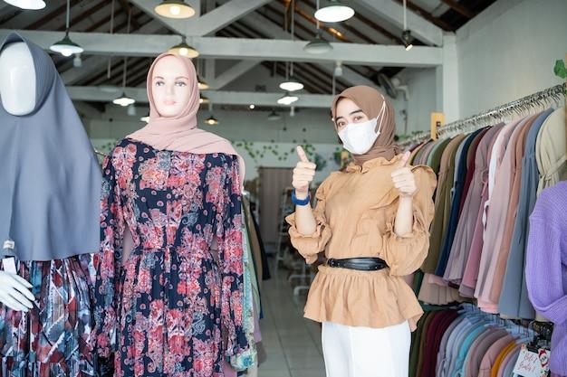 Een vrouw in een sluier die een masker draagt met duimen omhoog