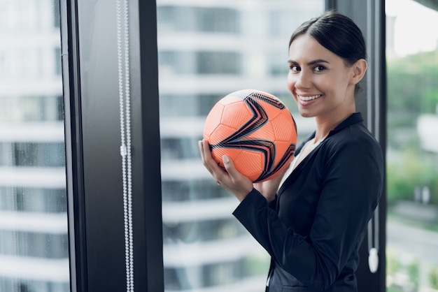 Een vrouw in een strak pak houdt een oranje voetbal.