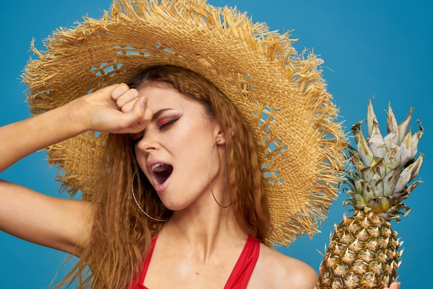 Een vrouw in een strooien hoed met een ananas in haar handen of is het een leuke blauwe achtergrond met exotisch fruit. hoge kwaliteit foto