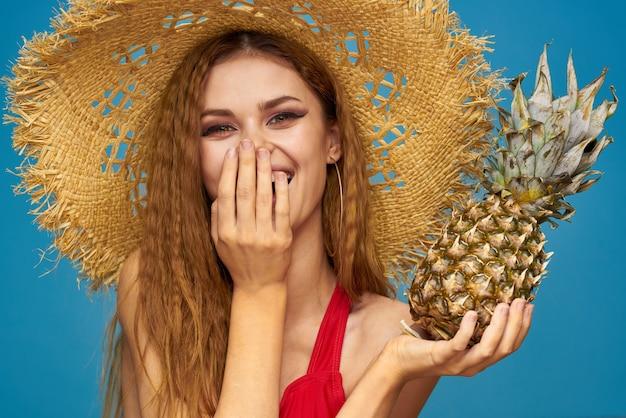 Een vrouw in een strooien hoed met een ananas in haar handen of is het een leuke blauwe exotische vrucht