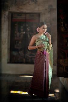 Een vrouw in een thaise jurk loopt met een lotusbloem om de monniken in de tempel te presenteren.