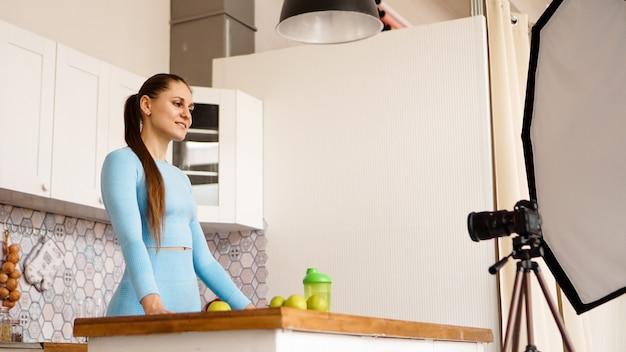 Een vrouw in een trainingspak neemt een videoblog op over sport en gezond eten. professionele apparatuur in de fotostudio met keukeninterieur