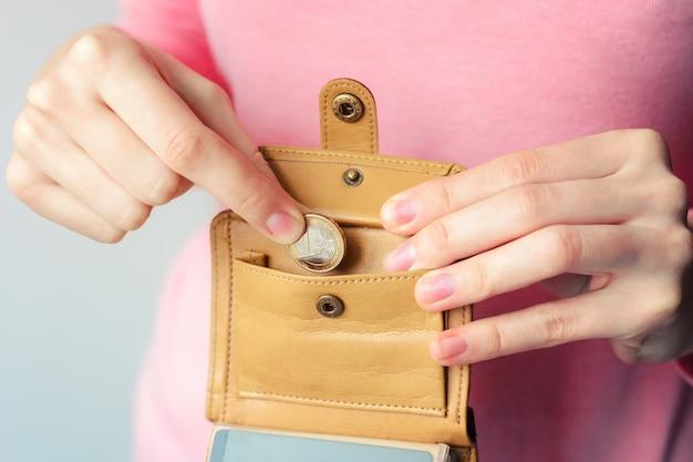 Een vrouw in een trui zet een euromunt in een bruine tas