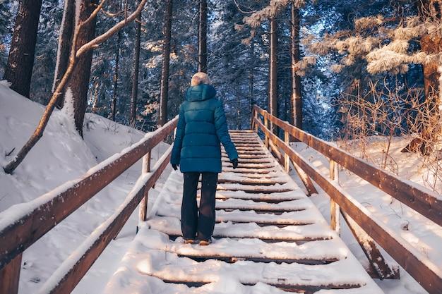Een vrouw in een turquoise donsjack staat met haar rug op een houten trap op een beboste heuvel. het concept van winterwandelingen in de frisse lucht.